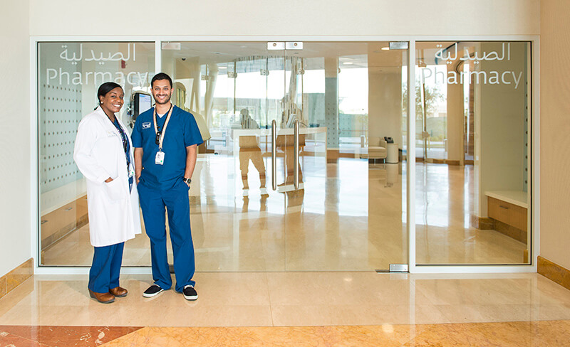 two staff members in blue scrubs standing in front of the Sidra Medicine pharmacy